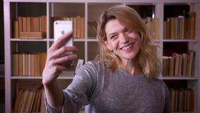 Pi?kny w ?rednim wieku blondynka nauczyciel robi atrakcyjnym selfies u?ywa? smartphone przy bibliotek? zbiory