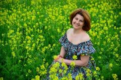 Piękny w średnim wieku kobiety obsiadanie w kwiatonośnej łące fotografia royalty free
