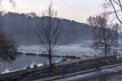Piękny widok śnieg na trawie w polu i jezioro obraz stock