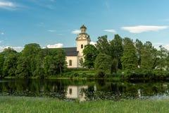 Piękny widok biały kościół rzeką otaczającą bujny obraz stock