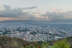 Piękny widok od wzgórza na dużym mieście z górami daleko fotografia stock