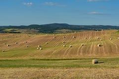 Piękny wieś krajobraz blisko Siena w Tuscany, Włochy Round słoma bel siana piłki w zbierającym niebieskim niebie i polach Zdjęcie Royalty Free