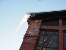 Piękny wielki przejrzysty sopel iluminujący słońcem wiesza od dachu dom zdjęcia stock