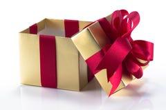 Piękny złoto teraźniejszości pudełko z czerwonym łękiem i faborkami Fotografia Stock