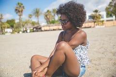 Piękny zadumany afro amerykański kobiety obsiadanie na plaży Obraz Stock