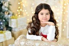 Piękny zakończenie w górę portraite kędzierzawa dziewczyna z złocistą Bożenarodzeniową girlandy magią zaświeca i drzewny dekoracj Fotografia Stock