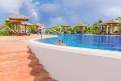 Piękny zapraszający widok wygodny wygodny pływacki basen z uśmiechającym się małej dziewczynki relaksującym dopłynięciem, cieszyć zdjęcia royalty free