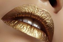 Piękny zbliżenie z żeńskimi tłuściuchnymi wargami z złocistym koloru makeup Moda świętuje makijaż, błyskotliwość kosmetyk fotografia stock
