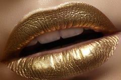 Piękny zbliżenie z żeńskimi tłuściuchnymi wargami z złocistym koloru makeup Moda świętuje makijaż, błyskotliwość kosmetyk Boże Na zdjęcie royalty free