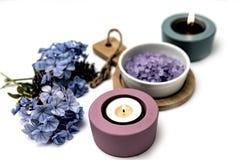 Piękny zdroju skład Błękita blask świecy na w i kwiaty fotografia royalty free