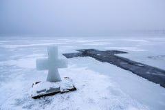 Piękny zima krajobraz z lodu krzyżem na zamarzniętej rzece na mgłowym ranku IV zdjęcia stock