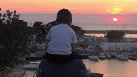 Piękny zmierzch na dennym chłopiec obsiadaniu na ramionach jego tata spojrzenia i cumuje przy quay jacht i żaglówka zbiory wideo