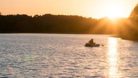Piękny zmierzch na jeziorze, rybacy na łodzi obrazy stock