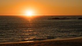 Piękny zmierzch na plaży w Portugalia jako słońce zamacza pod horyzontem obraz royalty free
