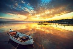 Piękny zmierzch nad spokojnym jeziorem i łodzią z niebem odbija i Zdjęcia Royalty Free