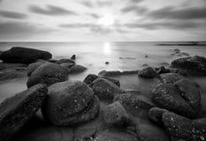 Piękny zmierzch przy kamienną plażą w czarny i biały Zdjęcia Stock