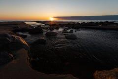 Piękny zmierzch z czerwoną piaska i wiosny wodą od rzecznego wyłażenia morze 13 - Veczemju Klintis Latvia, Kwiecień, - zdjęcia stock