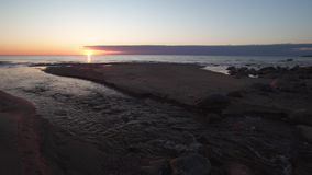 Piękny zmierzch z czerwonymi kolorami Tuja Latvia, Kwiecień, - 13, 2019 - Wodny spting wchodzić do morze - zdjęcie wideo