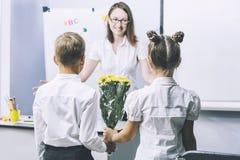 Pięknych dzieci dziecko w wieku szkolnym z kwiatami dla nauczycieli obraz stock