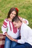 Pięknych potomstw ciężarna para ubierał w krajowy ukraiński stylowym mieć pinkin w jesień parku Macierzyński i rodzinny szczęście Zdjęcia Royalty Free
