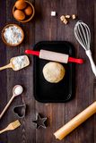 Piłka świeży surowy ciasto blisko ingedients i cookware na ciemnego drewnianego tła odgórnym widoku Obrazy Royalty Free