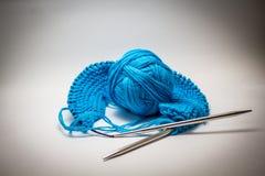 Piłka błękitna przędza na białym tle z dziewiarskimi igłami zdjęcia stock