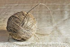 Piłka bieliźniane nici z dużą igłą na handmade szarym tablecloth z bliska Obraz Royalty Free