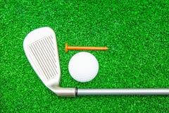 Piłka golfowa, żelazo i trójnik na sztucznej zielonej trawie, zdjęcie royalty free