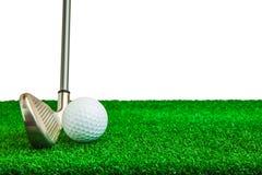 Piłka golfowa i żelazo na sztucznej zielonej trawie fotografia stock