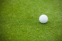 Piłka golfowa na zielonym gazonie Fotografia Royalty Free