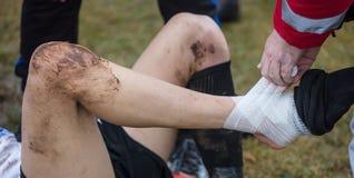 Piłka nożna, futbolowy pojęcie Zdradzony futbolista kłaść puszek na polu z kaleczenie kostką Zamazany tło, zamyka w górę widoku Zdjęcie Royalty Free