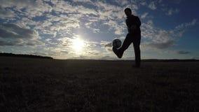 piłka nożna Mężczyzna faszeruje futbolowego piłki nożnej piłki sylwetki sport przy zmierzchu futbolu stylem wolnym zbiory wideo