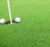 Piłki golfowe blisko dziury zdjęcia stock