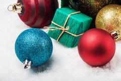 Piłki i prezenty na śniegu pod choinką Zdjęcie Stock
