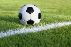 Piłki nożnej piłka siedzi na trawy polu z białym lampasem Fotografia Royalty Free
