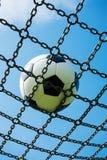 Piłki nożnej piłka w łańcuch sieci białym i czarnym futbolu, niebieskie niebo zdjęcie royalty free