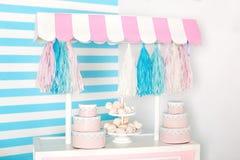 Pi?ce d'enfants avec le fond de rayure bleue zone de photo de stalle de sucrerie avec de grands macarons, bonbons et guimauves ch photographie stock libre de droits