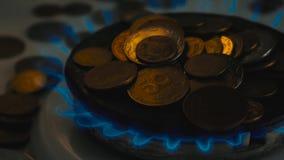 Pi?ces de monnaie de diff?rents pays sur un br?leur ? gaz Symbole des prix de carburant croissants banque de vidéos