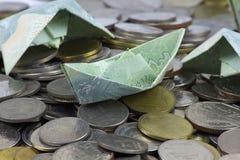 Pi?ces et billet de devise de la Tha?lande pli?s aux bateaux Art d'origami Argent de Tha?lande image stock