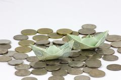 Pi?ces et billet de devise de la Tha?lande pli?s aux bateaux Art d'origami Argent de Tha?lande sur le fond blanc images libres de droits