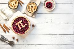 Pi Day Cherry and Apple Pies. Homemade traditional various Pies with Pi sign for March 14th holiday, on white wooden background, top view, copy space royalty free stock image