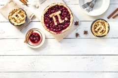 Pi Day Cherry and Apple Pies. Homemade traditional various Pies with Pi sign for March 14th holiday, on white wooden background, top view, copy space royalty free stock photography