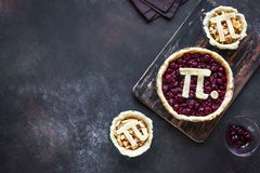 Pi Day Cherry and Apple Pies. Making homemade traditional various Pies with Pi sign for March 14th holiday, on rustic background, top view, copy space stock photos