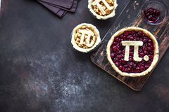 Pi Day Cherry and Apple Pies. Making homemade traditional various Pies with Pi sign for March 14th holiday, on rustic background, top view, copy space royalty free stock image
