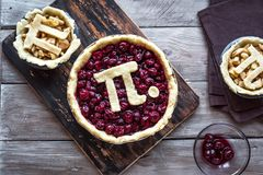 Pi Day Cherry and Apple Pies. Making homemade traditional various Pies with Pi sign for March 14th holiday, on rustic wooden background, top view, copy space stock images