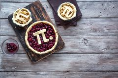 Pi Day Cherry and Apple Pies. Making homemade traditional various Pies with Pi sign for March 14th holiday, on rustic wooden background, top view, copy space royalty free stock photos