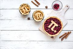 Pi Day Cherry and Apple Pies. Making homemade traditional various Pies with Pi sign for March 14th holiday, on white wooden background, top view, copy space royalty free stock image