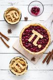 Pi Day Cherry and Apple Pies. Making homemade traditional various Pies with Pi sign for March 14th holiday, on white wooden background, top view stock images