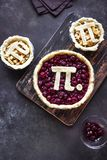 Pi Day Cherry and Apple Pies. Making homemade traditional various Pies with Pi sign for March 14th holiday, on rustic background, top view, copy space stock photography