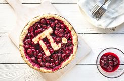 Pi Day Cherry Pie. Homemade Traditional Cherry Pie with Pi sign for March 14th holiday, on white wooden background, top view, copy space stock image